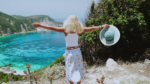 Lifestyle travel happiness concept young blonde tanned woman with hat in raised hands and hairs Live Action
