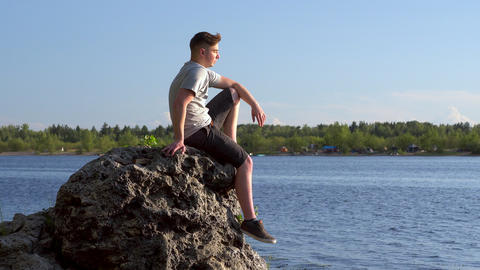 A young man sits on a stone by the river and admires nature. A man in nature Live Action
