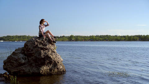 A young woman sits on a stone by the river and admires nature. Girl in nature Live Action