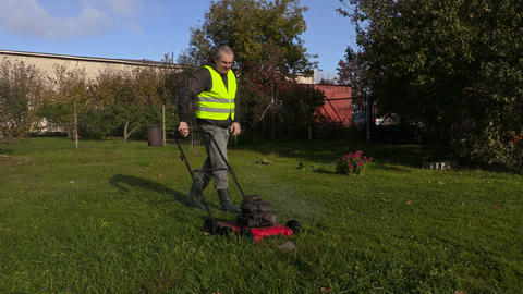 Worker pushing lawnmower and remove stone from lawn Footage