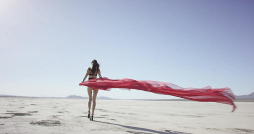 Girl with a fabric walking and dancing in the desert Footage