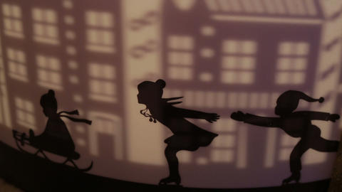 Decorative silhouettes of children skating on a sled and projection of city Footage