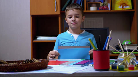 Serious Boy in Blue T-Shirt Raises Hands and Shows Blue on Colored Paper Live Action