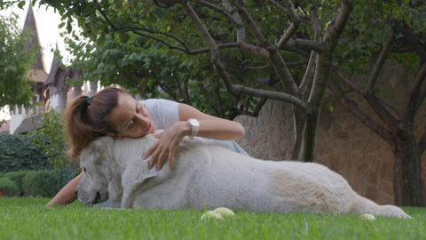 Woman gives dog a kiss and cuddle, close loving relationship between pet and Live Action