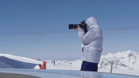 Photographer with a telephoto camera that takes pictures on a mountain plateau w Footage