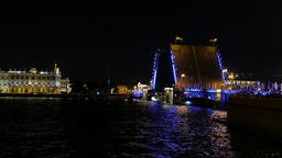 Decorate lit bascule bridge drawn up at night time, small sail boat pass through Footage