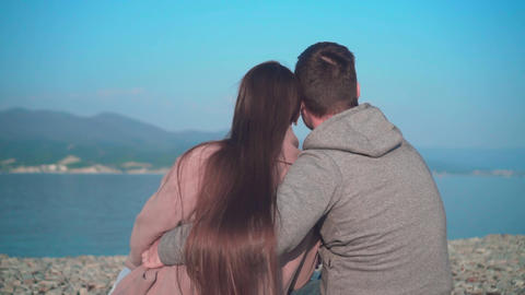 A young girl with a guy sitting hugging on the beach in the spring. The girl and Live Action