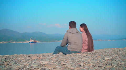 Young girl with a guy sitting on the beach. The girl lays her head on the guy's Live Action