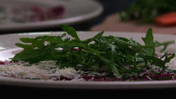 Serving carpaccio meat dish falling green herbs rucola slow motion HD video Footage