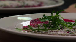 Serving carpaccio meat dish green herbs rucola slow motion сlose up HD video Footage