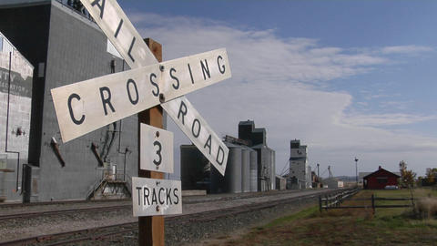 A railroad crossing sign stands near multiple grain silos Footage