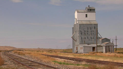 An abandoned grain elevator stands along a stretch of railway track Footage