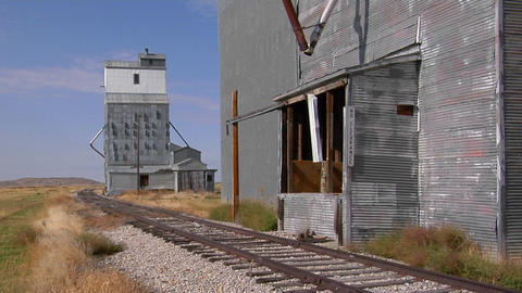 Abandoned grain elevators stand along a rusty stretch of railway track Footage