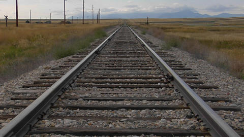 Railroad tracks stretch across a grassy plain into the horizons Footage