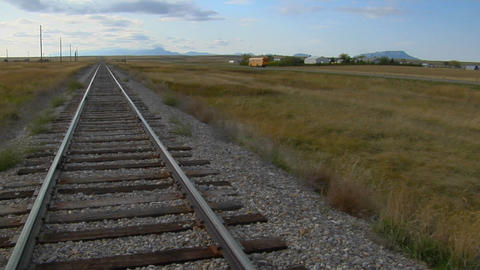 A school bus passes an old railroad track that lays across a prairie Footage