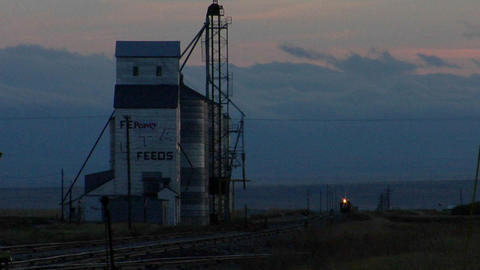 A train approaches a grain elevator Stock Video Footage