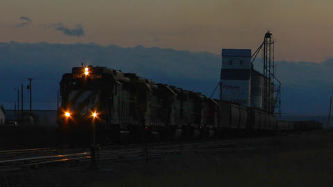 A freight train passes a grain silo at dusk Stock Video Footage