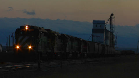 A freight train passes a grain silo at dusk Footage