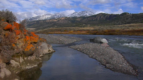 A small stream runs beneath snow covered mountains in... Stock Video Footage
