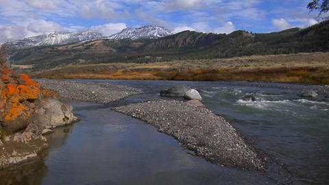 A small stream runs beneath snow covered mountains in Yellowstone National Park Footage
