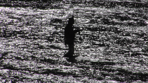 A man fly fishes in a broad shallow river Stock Video Footage