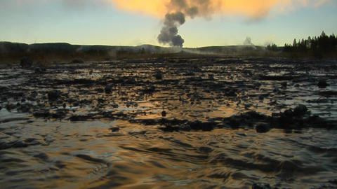 Hot water runs from a volcanic geyser sending steam into... Stock Video Footage