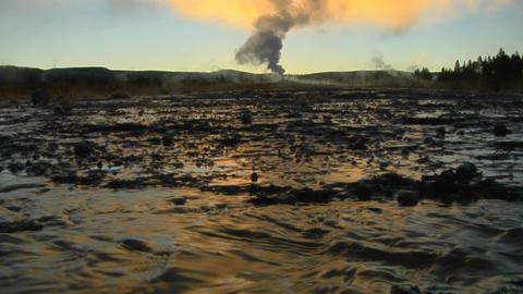 Hot water runs from a volcanic geyser sending steam into the sky in a geothermal area at Yellowstone Footage