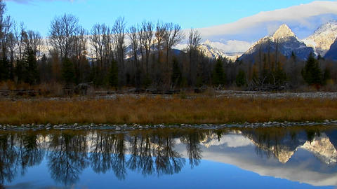 The Grand Teton mountains are perfectly reflected in a... Stock Video Footage