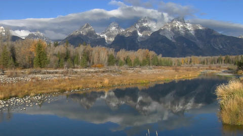 The Grand Teton mountains are reflected in a mountain lake Footage