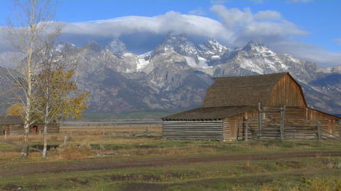 An old barn stands with the Grand Teton mountains in the... Stock Video Footage