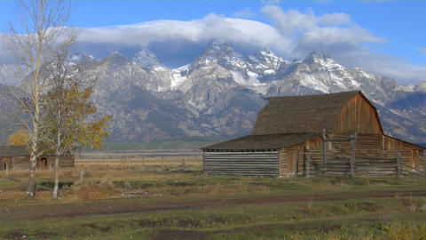 An old barn stands with the Grand Teton mountains in the background Footage