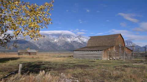 An old barn with an attached corral slowly deteriorates near the Grand Teton mountains Footage