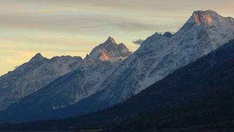 Pink sunlight graces the tips of a mountain pass in the Grand Tetons Footage