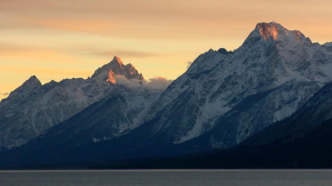 Orange light brushes the tips of the mountain peaks in... Stock Video Footage