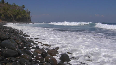 Ocean waves roll onto a rocky beach Footage