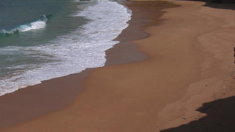 Blue green waves wash onto a sandy beach Stock Video Footage