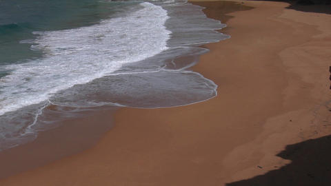 Blue green waves wash onto a sandy beach Footage