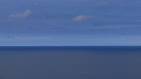 A calm blue sea sits under a blue sky Stock Video Footage