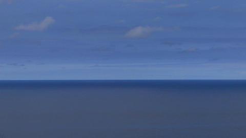 A calm blue sea sits under a blue sky Footage