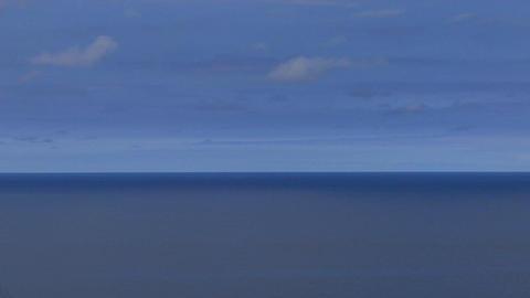 A calm blue sea sits under a blue sky Stock Video Footage