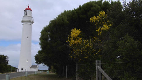 A lighthouse stands under an overcast sky Stock Video Footage