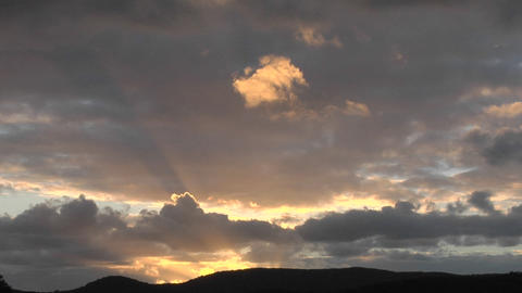 The rays of the sun peek through clouds over a mountain... Stock Video Footage