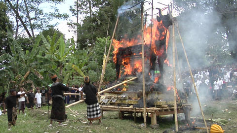 Men use long poles to poke at a funeral pyre during a cremation ceremony in Bali Footage
