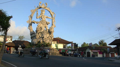 A giant statue of a Hindu god stands at the center of an intersection in Bali, Indonesia Footage