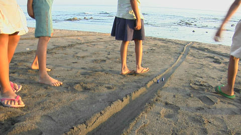 Bali children play a game, rolling bottle caps down the beach Footage