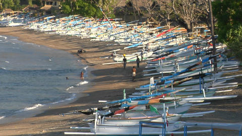 Tourists walk in and out of the water at a beach lined with longboats Footage