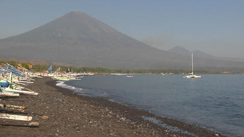 Catamarans are beached along a shore at the base of a volcano Footage