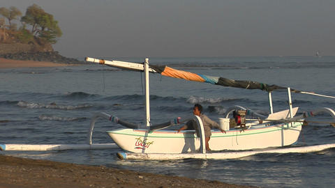 Boys push a catamaran-style fishing boat to shore in... Stock Video Footage