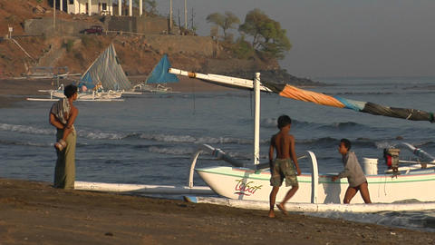Boys push a catamaran-style fishing boat to shore in Indonesia Footage