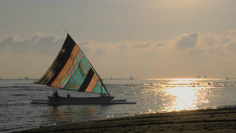 A colorful sailboat approaches a shoreline Stock Video Footage